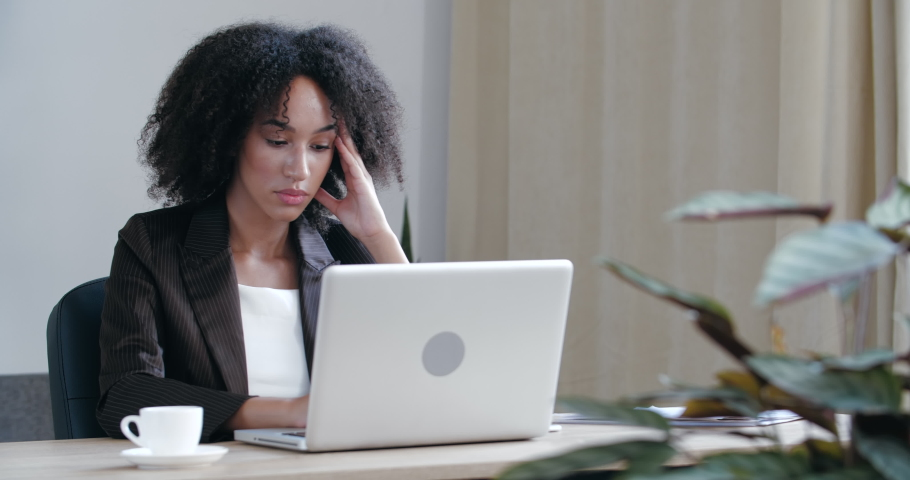 Pensive girl sits at home at table with laptop, processes information, business woman frowns serious face, solves difficult problem test conducts analysis research online Internet looking for solution