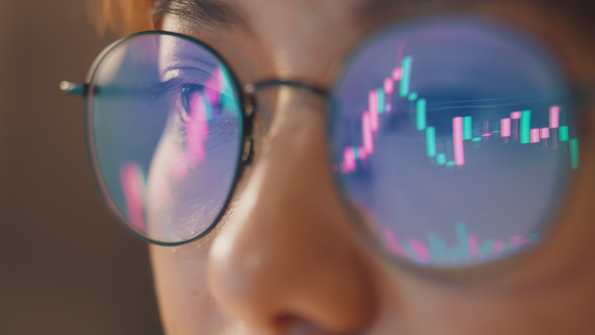 Closeup - Female eyes in eyeglasses late at night scrolling in front of laptop. Coder, she checking Bitcoin price chart on digital exchange on smartphone, cryptocurrency future price action prediction Royalty-Free Stock Footage #1072935389