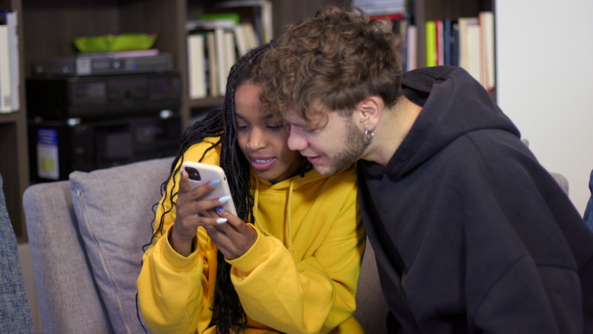 Young couple looking at video on smartphone. Boyfriend and girlfriend having fun with cell phone for internet and social media. Happy people with mobile telephone for technology at home Royalty-Free Stock Footage #1072936523