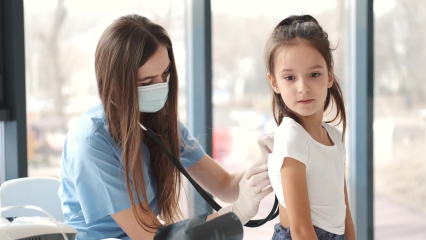 Female doctor examining girl's breathing with stethoscope Royalty-Free Stock Footage #1072995590