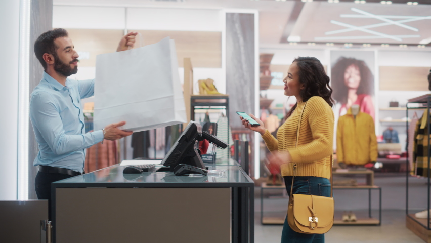 Clothing Store: Young Woman at Counter Buys Clothes from Friendly Retail Sales Assistant, Paying with Contactless NFC Smartphone Touching Terminal. Trendy Fashion Shop with Designer Brands.