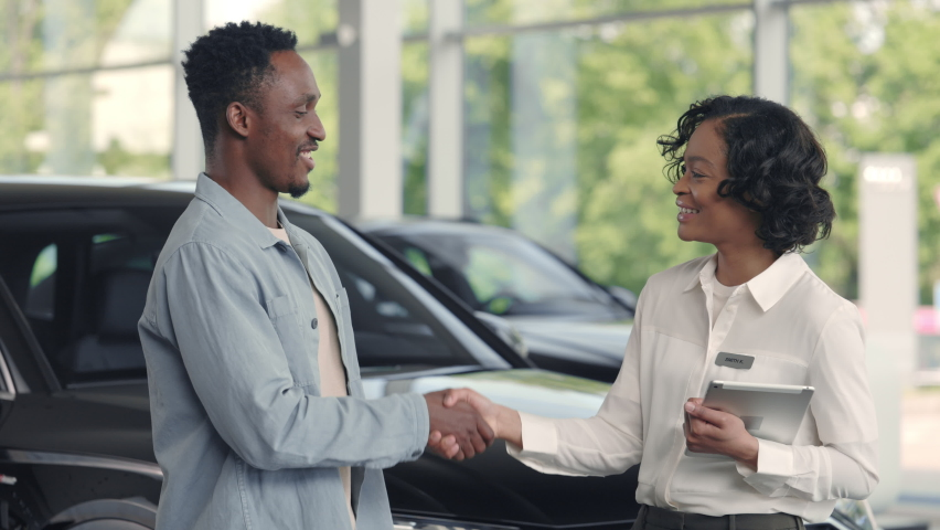 Female car dealer in formal clothes shaking hands with male customer at auto salon. African man signing agreement on digital tablet. Expensive purchase.
