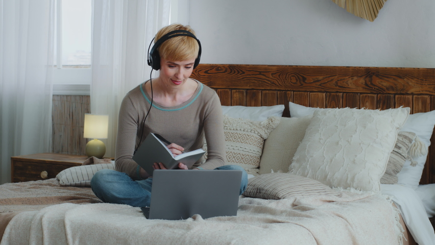 Smiling beautiful woman in headphones stay at home during quarantine looking at laptop screen, use video call app watching educational lecture, writing notes in copybook, sitting on comfortable bed
