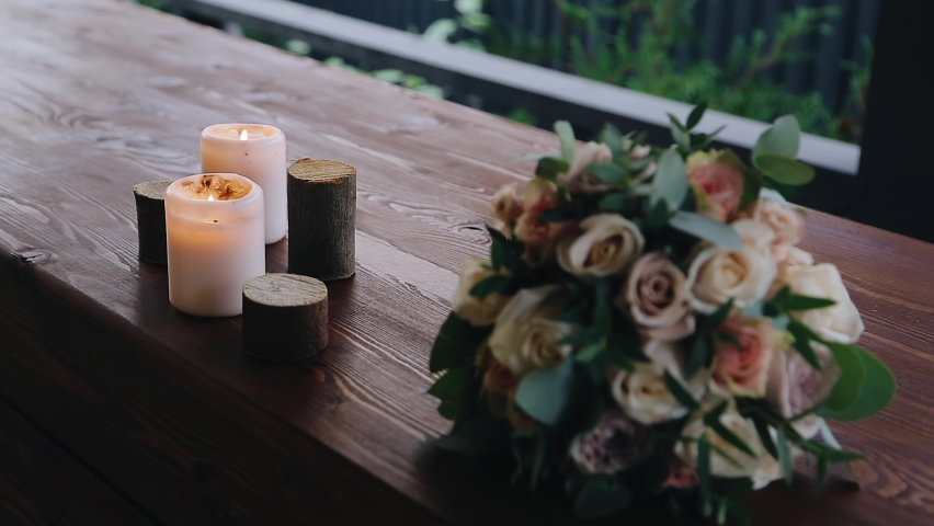 A bouquet of flowers lies on the wooden windowsill and two burning candles stand next to it. Close-up shooting Royalty-Free Stock Footage #1073329721