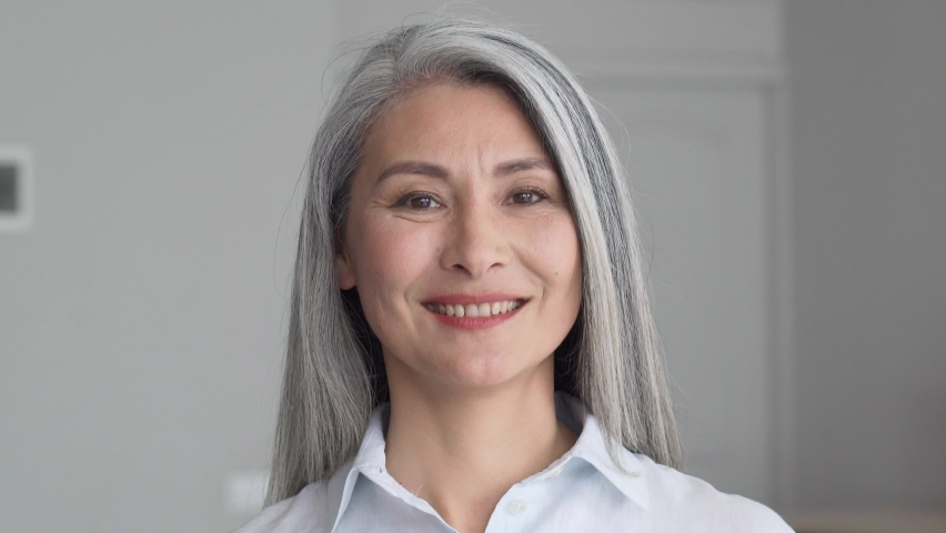 Happy smiling stylish confident 50 years old Asian female professional standing looking at camera at gray background. Portrait of sophisticated grey hair woman advertising products and services. Royalty-Free Stock Footage #1073342420