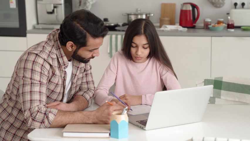 Young indian dad helping teenage daughter schoolgirl study online at home sitting at kitchen table at home using pc laptop computer. Father and kid e learning together having remote distant lesson. Royalty-Free Stock Footage #1073362646