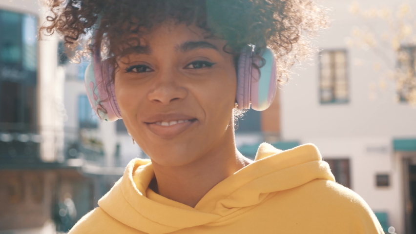 Beautiful black woman with afro curls hairstyle.Smiling model in yellow hoodie.Sexy carefree female enjoying listening music in wireless headphones.Posing on the street background at sunset. Dancing