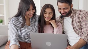 Parents with teenage daughter watching funny videos using laptop browsing online tv streaming enjoying spending time together on weekend at home in living room sitting on sofa. Happy indian family.