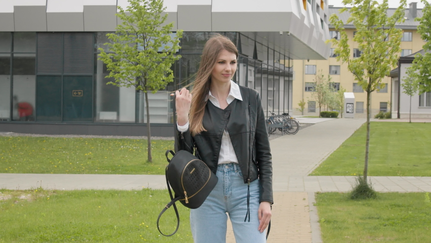 Young girl student, teenager, in a leather jacket with a backpack, stylishly dressed, runs looking at the camera and smiling. Very Slow Movement. Portrait woman, outdoor walking in park, generation z