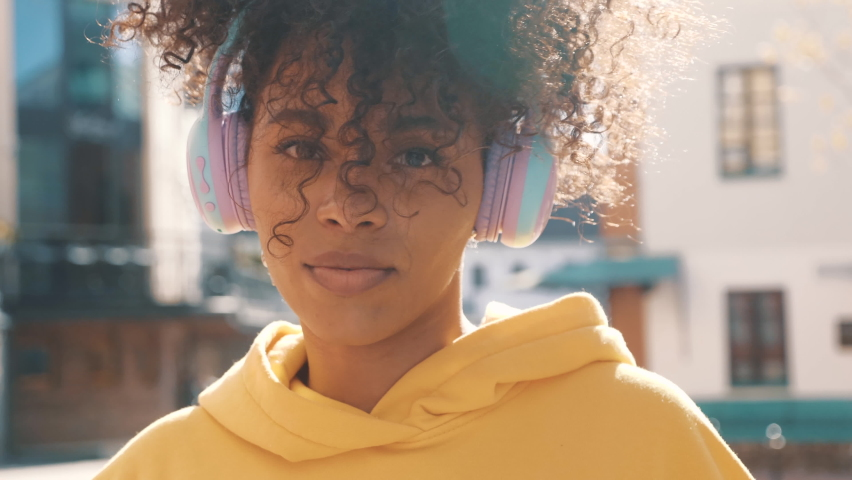 Beautiful black woman with afro curls hairstyle.Smiling model in yellow hoodie.Sexy carefree female enjoying listening music in wireless headphones.Posing on the street background at sunset