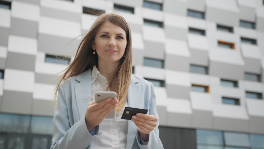 Smiling young woman customer holding credit card and smartphone. Happy female shopper using instant easy mobile payments making purchase in online store. E-banking app service. Online shopping. Royalty-Free Stock Footage #1073456180