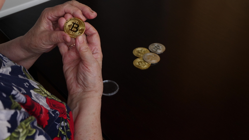 An elderly woman with surprise opens the box and examines the bitcoin cryptocurrency gift. Other bitcoins are in a heap on the table. Blockchain technology, bitcoin mining.
