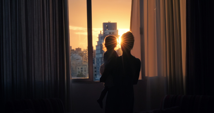 Family watch sunset. Woman walks towards open window with kid in her hands and they both enjoy sunset in the city   Shutterstock HD Video #1073534345
