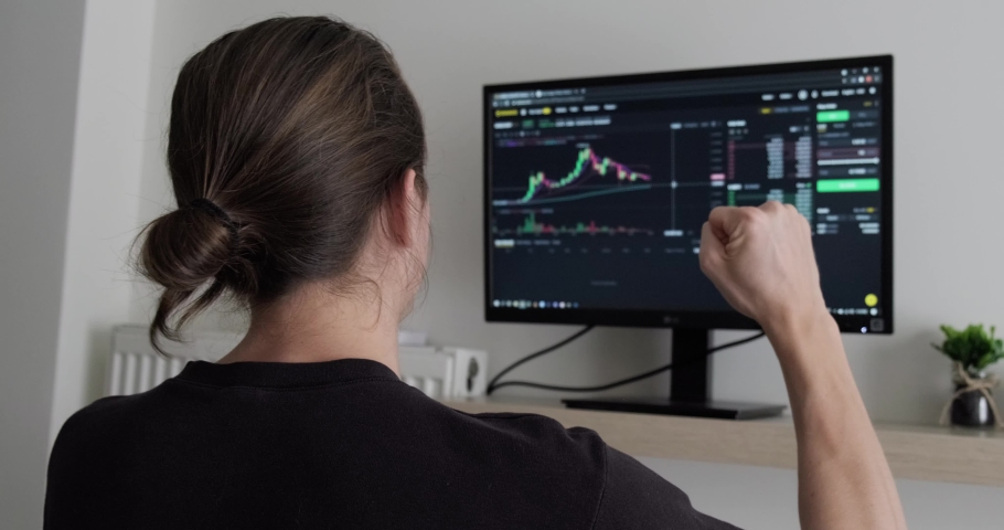 Happy man cheering in front of monitor with finance charts, crypto currency successful trading, investing online, working from home.