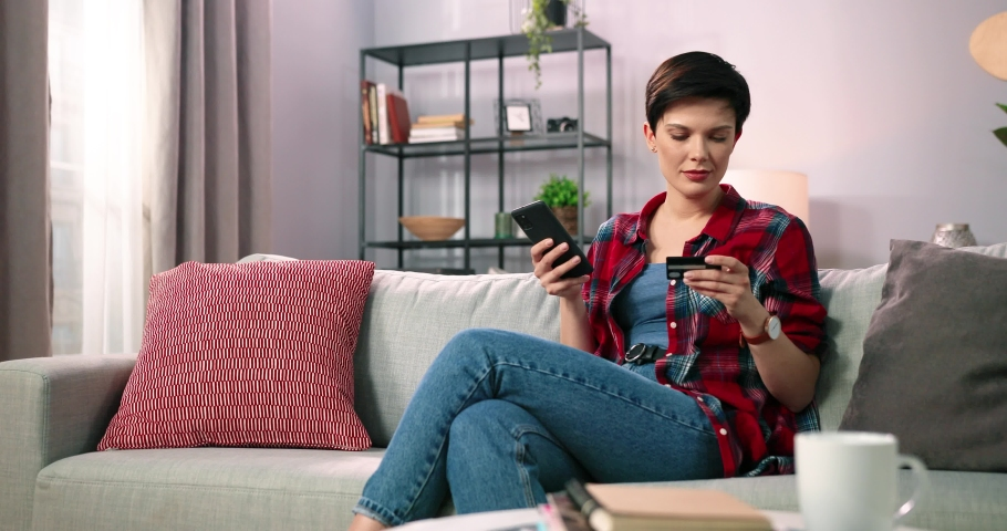 Beautiful woman with stylish short haircut at home sitting on sofa in rejoices successful replenishment of bank card with mobile application. Royalty-Free Stock Footage #1073598212