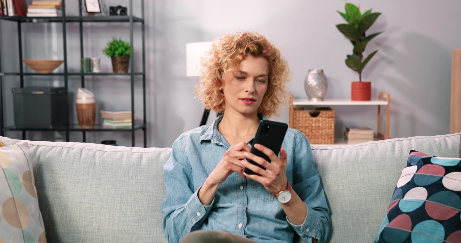 Close up of beautiful blonde woman with curly hair sitting at home on couch and rejoices replenishing bank account holding card and smartphone. Royalty-Free Stock Footage #1073598275