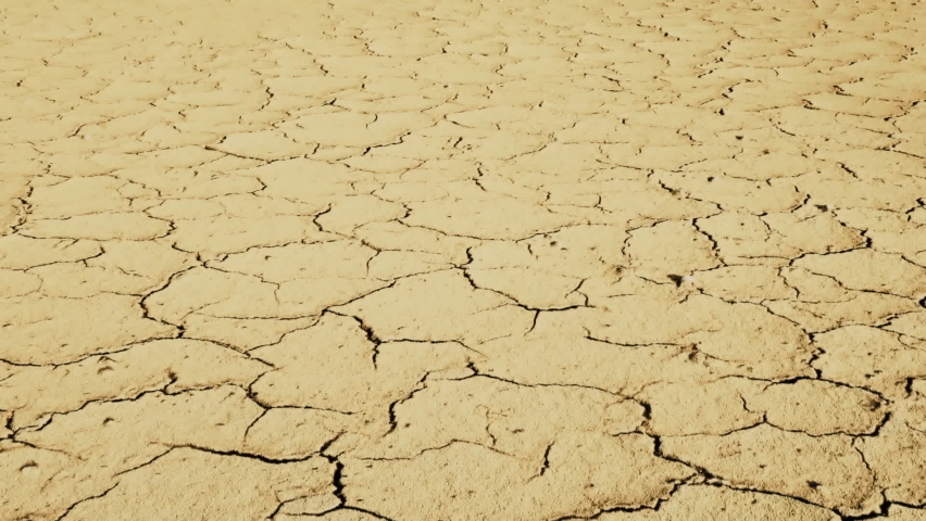 Cracked soil in a desert drying out, Slow motion on dolly. Global climate change and drought. Dry cracked ground. Temperature rise, global warming, environment and ecology. High quality Full HD video. Royalty-Free Stock Footage #1073599778