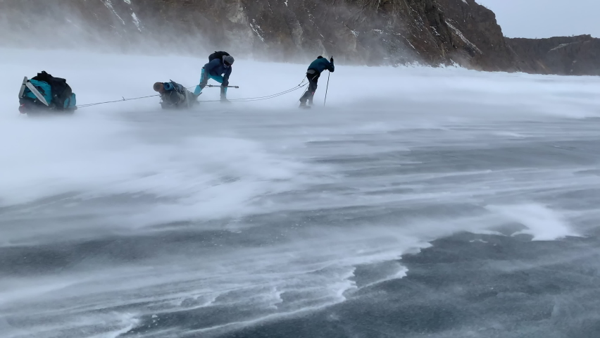 Two men are blown away by a hurricane wind with a blizzard during a hike across frozen Lake Baikal with sledges equipped with backpacks in winter. Storm on Lake Baikal in winter