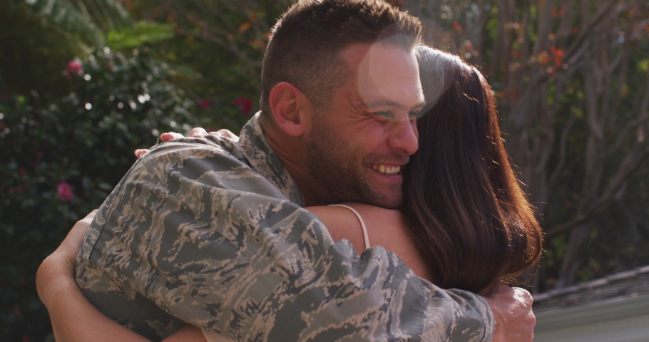 Smiling caucasian male soldier embracing his happy wife in garden outside their house. soldier returning home to family.