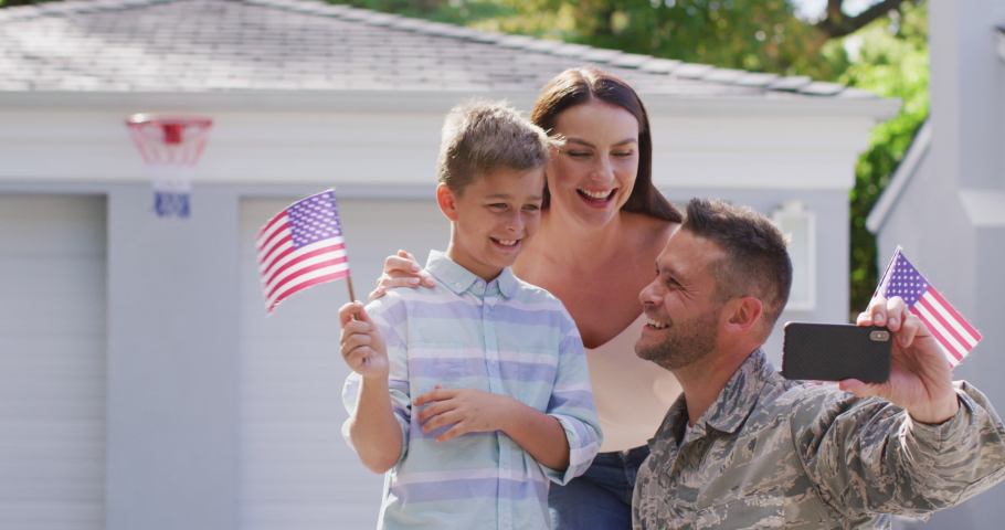Happy caucasian male soldier taking selfie with smiling son with wife in garden outside their house. soldier returning home to family.