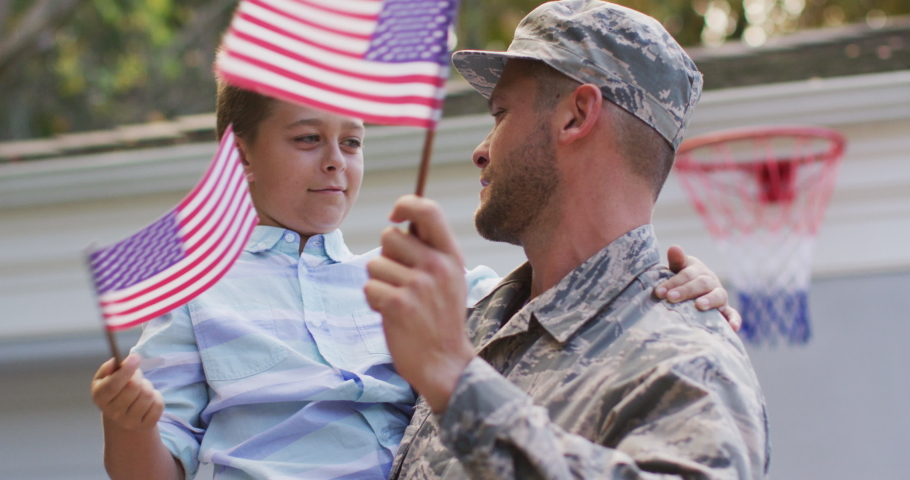 Happy caucasian male soldier carrying his smiling son holding flag in garden outside their house. soldier returning home to family.