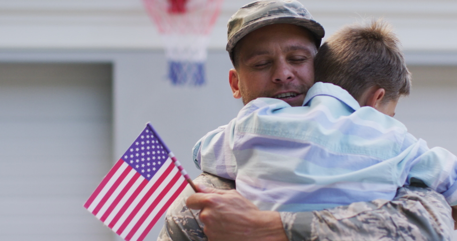 Happy caucasian male soldier hugging his smiling son holding flag in garden outside their house. soldier returning home to family.