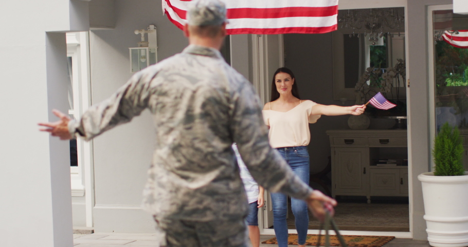 Caucasian male soldier greeting son and wife in garden with american flag hanging outside house. soldier returning home to family.