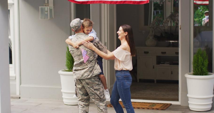 Happy caucasian male soldier lifting son and greeting wife outside their house. soldier returning home to family.