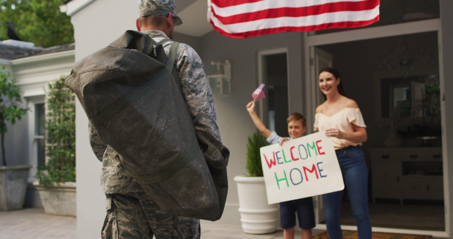 Happy caucasian male soldier greeting son and wife with welcome home sign outside their house. soldier returning home to family.