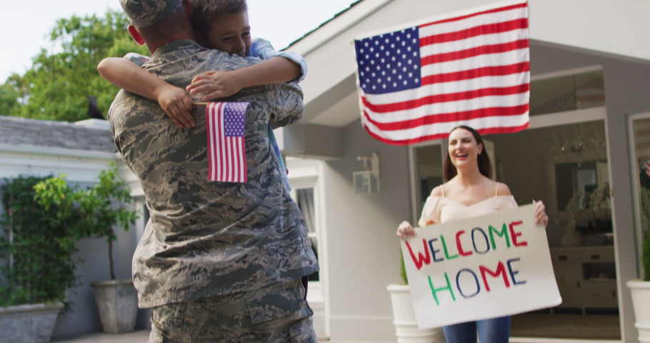 Caucasian male soldier greeting happy son and wife with welcome home sign outside their house. soldier returning home to family.