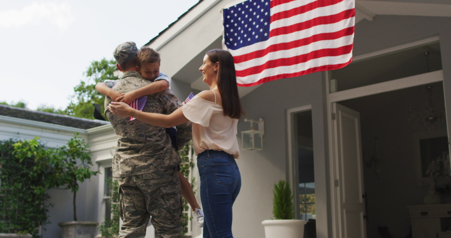 Happy caucasian male soldier lifting son and greeting wife with flag hanging outside their house. soldier returning home to family.