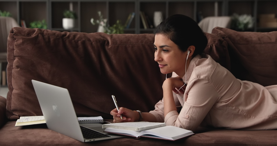 Indian woman student lying on sofa use laptop makes assignment, writes notes in copybook while listens audio course through wired earphones. E-learn study, prepare for university exam process concept