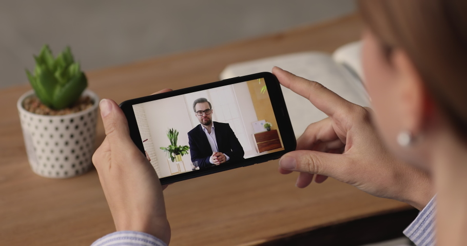 Employee sit at desk hold smartphone listens to boss instructions by videocall, device screen over shoulder. Businesswoman watch webinar online video receiving helpful info. Video call event concept