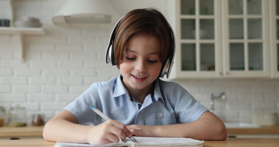 Pretty little 6s 7s boy wear headphones communicates to on-line tutor, writing notes in copybook studying subject use videocall app. Young gen and modern tech, internet, videoconference usage concept