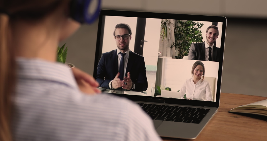 Businesspeople involved in group videocall, remote negotiations, business solution, virtual meeting, laptop screen over businesswoman shoulder. Video call event, comfort usage of modern tech concept