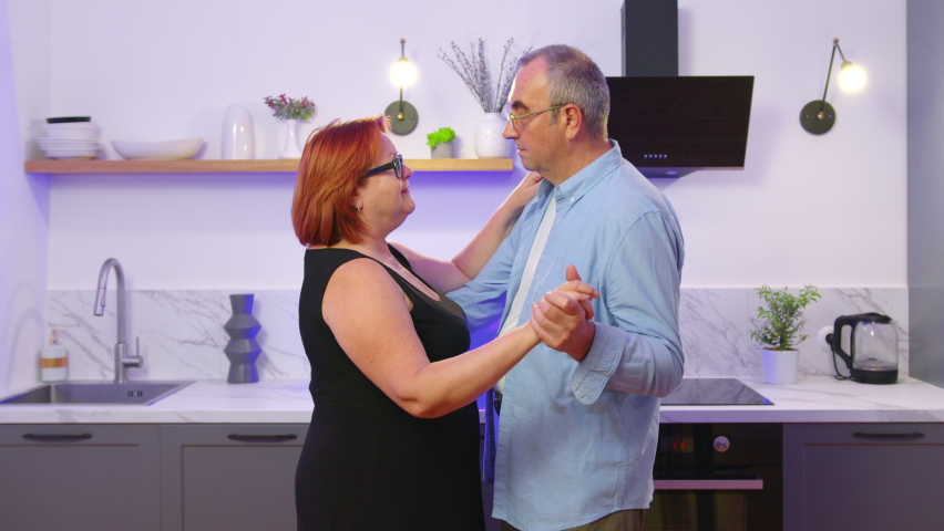 Happy mature senior couple dancing laughing in the kitchen, beautiful romantic middle aged older grandparents relaxing having fun together at home celebrating anniversary enjoy care love tenderness.