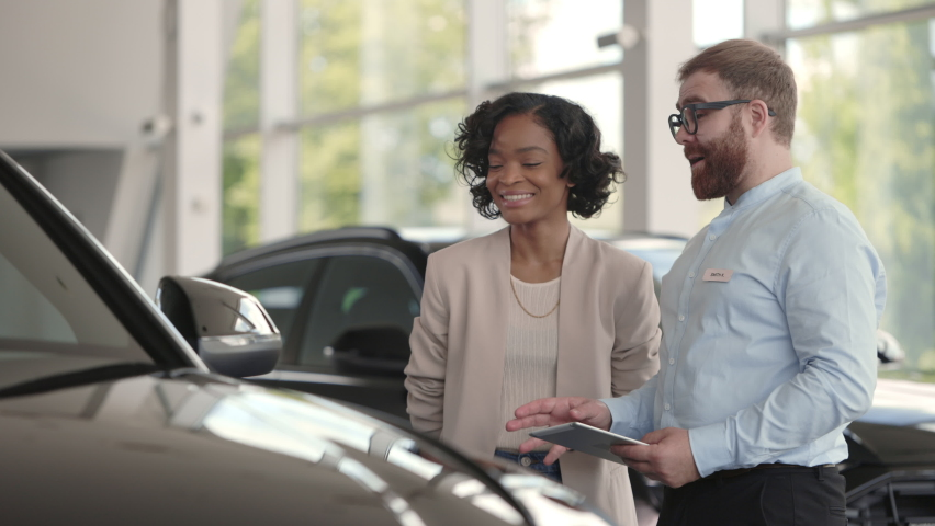Bearded male dealer using digital tablet while presenting to charming african woman new model of luxury car. Happy female customer choosing new vehicle to buy at showroom.