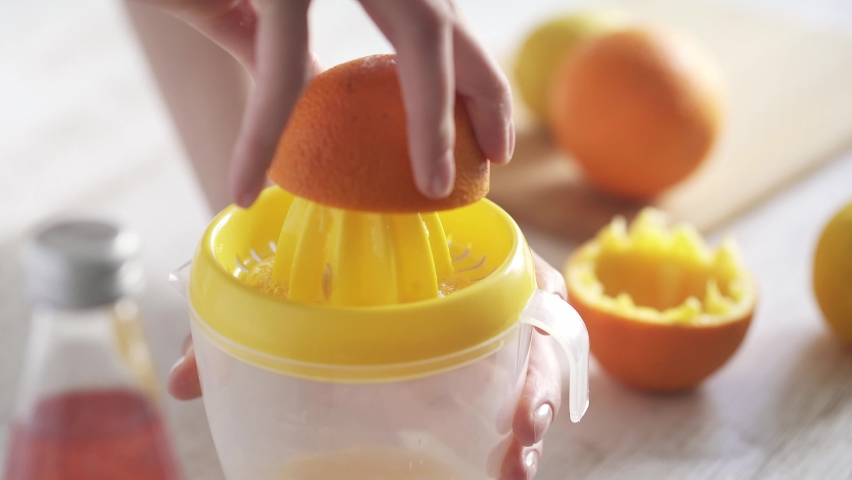 A woman squeezes orange juice from a bright orange fruit. Juicing an orange. Preparing orange juice for breakfast in the sunny kitchen. Juicing with a citrus juicer.