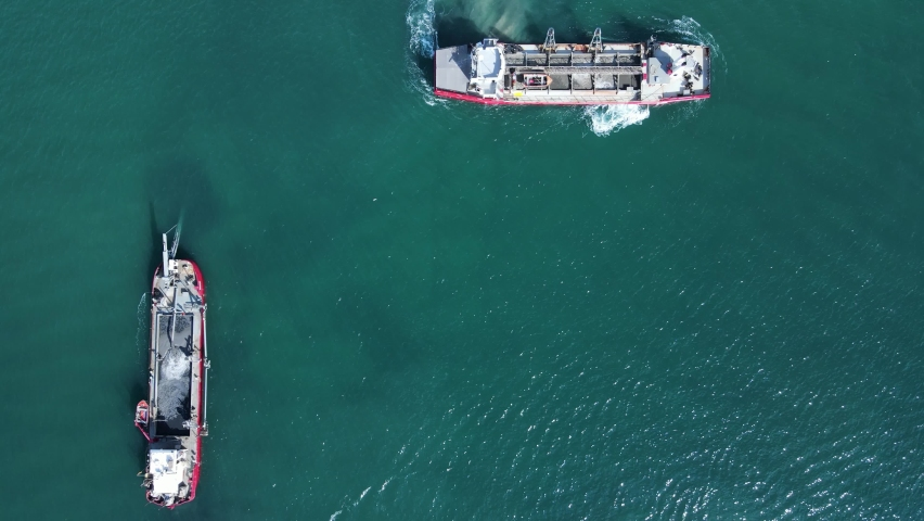 Two large sand dredging vessels positioned in a city shipping channel to re built up sand from the waterway. High drone view looking down   Shutterstock HD Video #1074237749