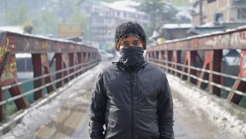 A young Indian Asian man in winter jacket standing in the middle of the snow-covered road or bridge wearing a face protective mask looking at the camera amid COVID 19 epidemic or pandemic Royalty-Free Stock Footage #1074311369