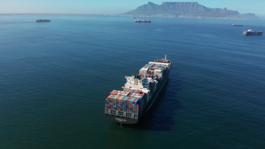 A large container ship for transporting goods near the port of Capetown, South Africa. A container ship carries cargo across the ocean. Transportation. Delivery. Logistics. Aerial 4K shot.