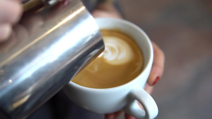 Hands of a blonde woman barista making coffee drawings with milk in a cup in a coffee shop   Shutterstock HD Video #1074380315