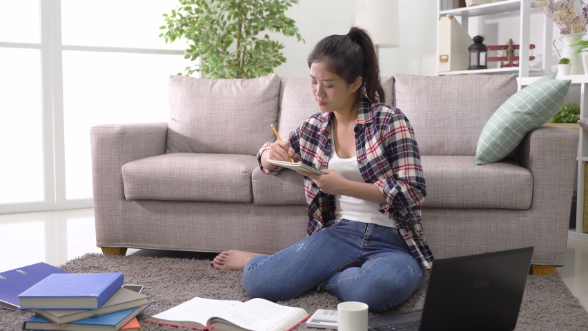 asian chinese female high school student sitting on carpet scattered with electronic devices and books is making study plans at home Royalty-Free Stock Footage #1074388259