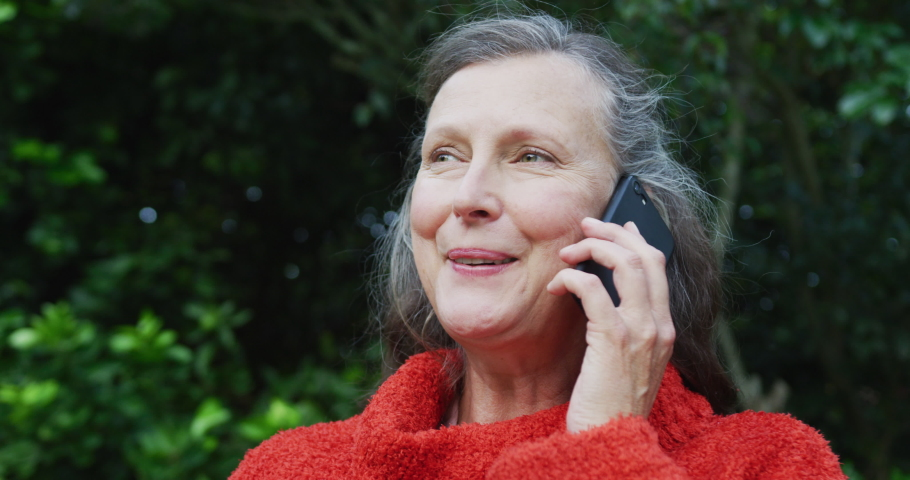 Happy senior caucasian woman sitting in garden, looking around and talking on smartphone. retirement lifestyle with communication technology at home.