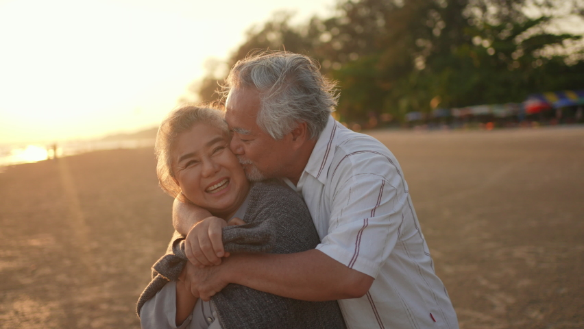 Happy Asian family senior husband cover his wife with a blanket and hugging together on the beach at summer sunset. Healthy elderly retirement couple relax and enjoy romantic outdoor vacation together | Shutterstock HD Video #1074441485