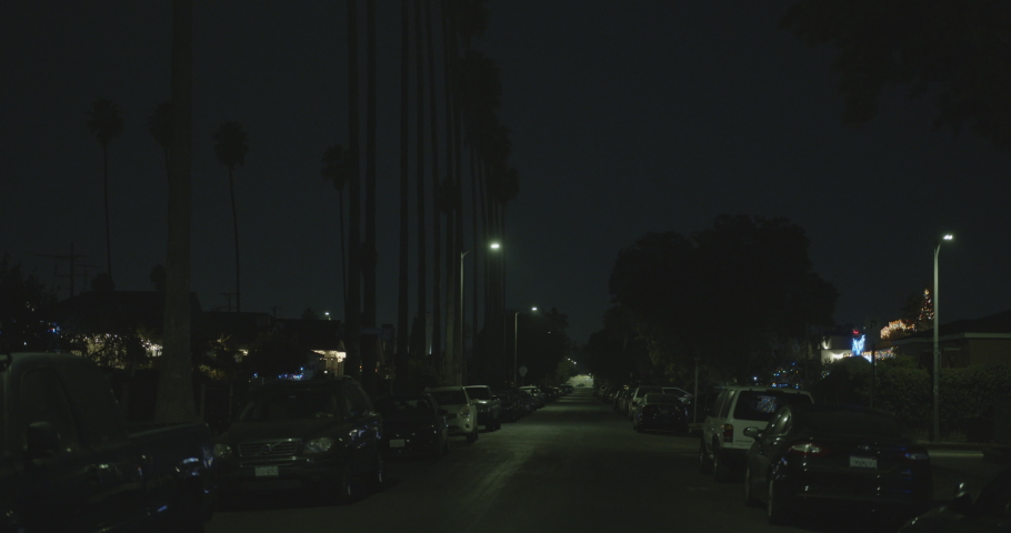 Los Angeles, CA , USA -  11 19 20 :  4K Urban night street footage with cars parked and palm trees