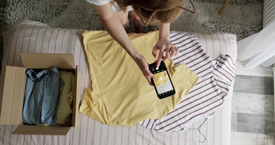 Woman taking photo of used shirt to sell online, second hand clothes resale or donation concept, sustainable living, pre owned clothing. Royalty-Free Stock Footage #1074538790