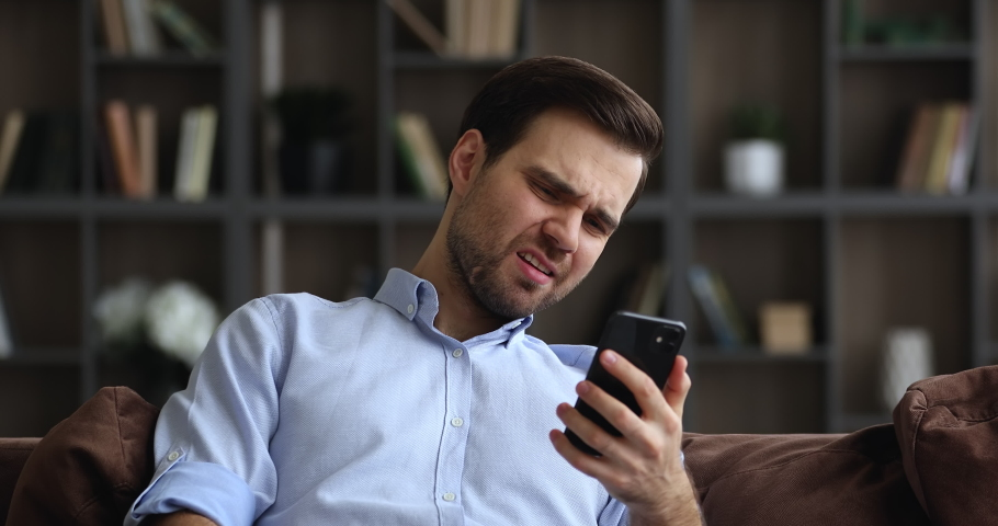 Bad sms news, device problem, app crash concept. Young man sit on sofa in living room holding smartphone read negative message feels annoyed, having gadget trouble, lost wi-fi connection, e-mail spam