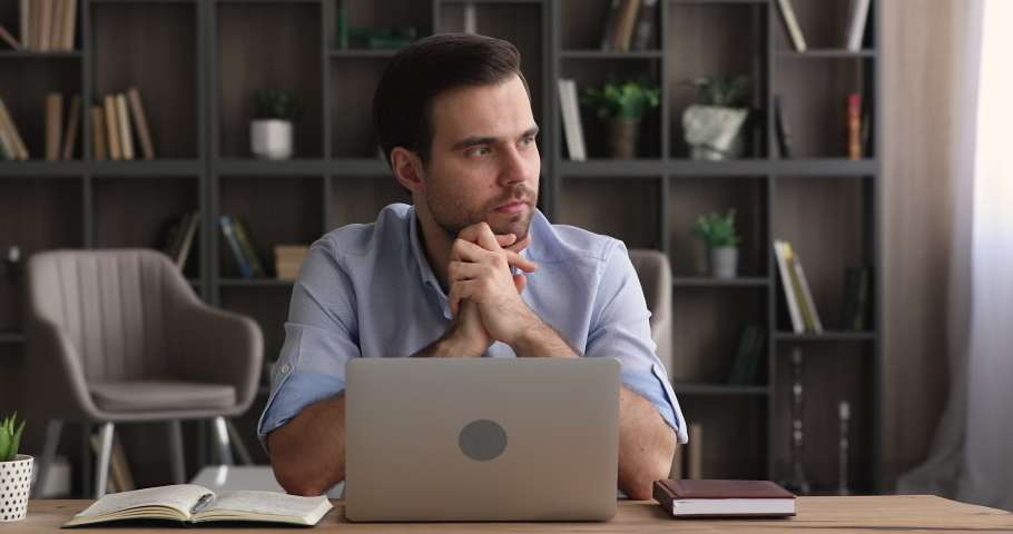 Brooding serious 35s freelancer man sit at table in comfortable home office room work on laptop looks concentrated thinking over business issue solution, makes telecommute job use modern tech concept Royalty-Free Stock Footage #1074542429