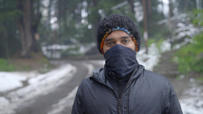 A young Indian Asian man in winter jacket standing along the the snow-covered road or bridge wearing a face protective mask looking at the camera amid COVID 19 epidemic or pandemic Royalty-Free Stock Footage #1074609749